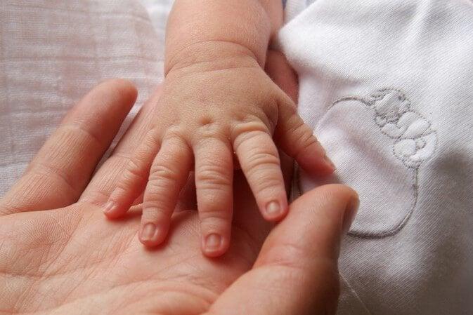 Babyhånd i en voksens hånd