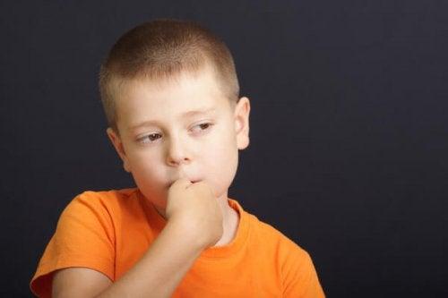 en gutt suger på tommelen sin