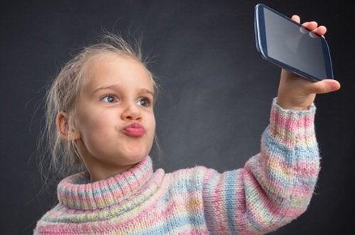 barn holder mobiltelefon ta selfie