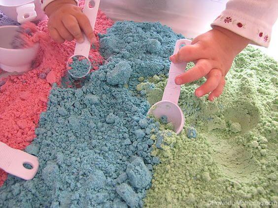 La barna dine grave med hendene i magisk sand!