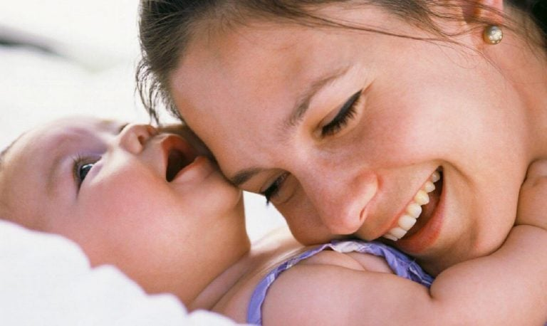 mor smiler med baby