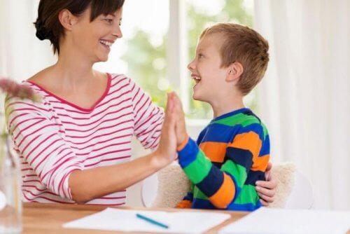 Mor gir high five til et barn med Autismespekterforstyrrelser