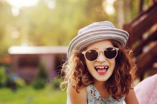 En glad jente med solbriller.