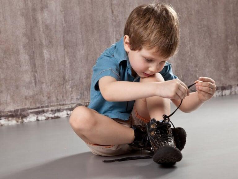 Liten gutt knyter skoene sine