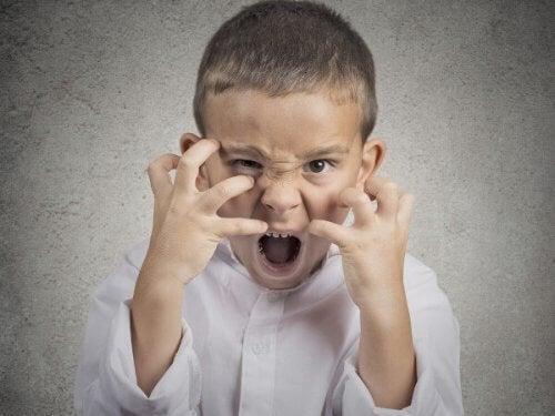 En gutt oppfører seg sint og aggressiv.