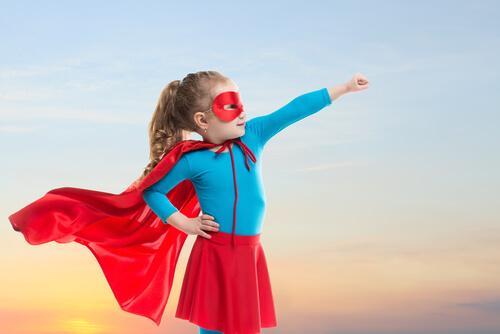 En jente kledd som en superhelt med kappe og maske.