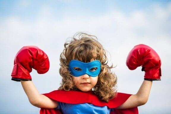 En jente kledd som en superhelt med maske og hansker.