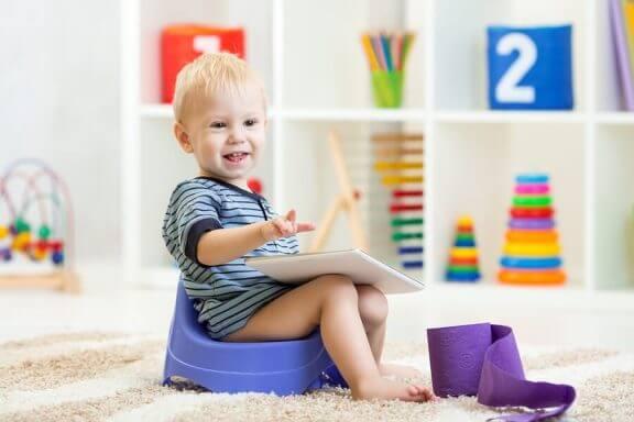 En gutt som sitter på en potte med en notatbok på knærne.