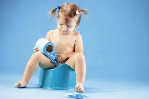 En jente som sitter på en blå potte med dopapir.