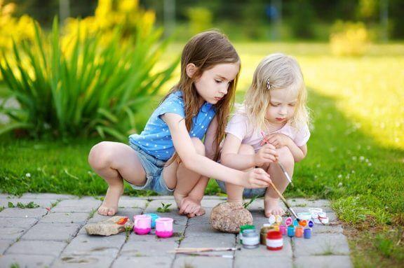 To barn som leker med maling ute.