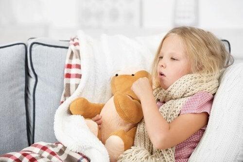 En syk jente som sitter med en bamse og hoster.