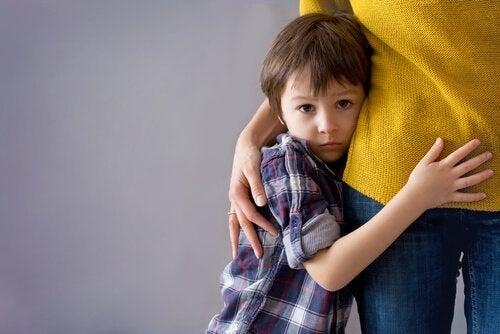 En gutt som holder seg fast i moren sin.