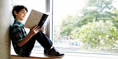 En gutt som sitter i en vinduskarm og leser.