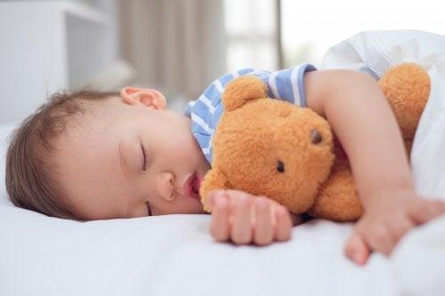 Et barn som sover med en bamse i armene.