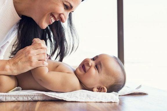 En mor lent over en baby på et bord.