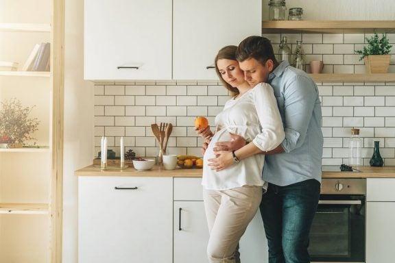 Et gravid og lykkelig par på et kjøkken.