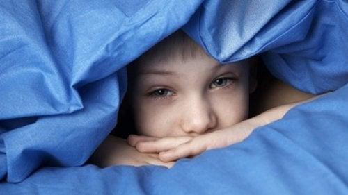 En gutt har gjemt seg under dynen.