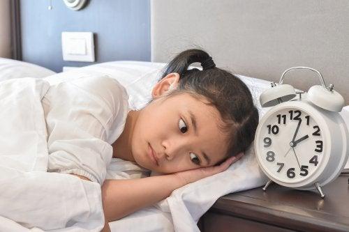 En jente som ligger i en seng og ser på en vekkeklokke.