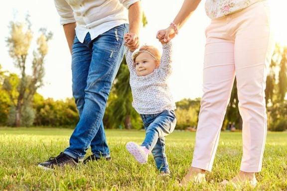 Et lite barn som går mellom foreldrene sine.