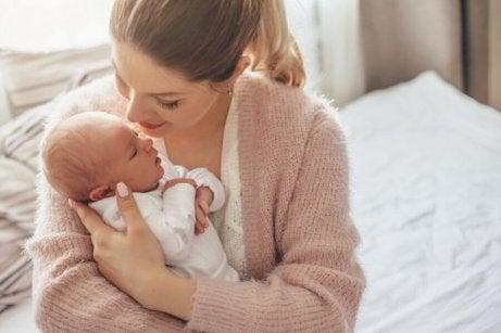 En mor som sitter med babyen sin