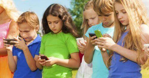 Barn som er opptatt med mobiltelefonene sine