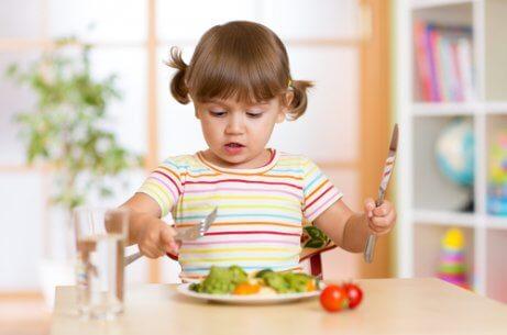 En ung jente spiser salat.