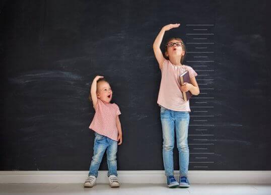 To søstre måler høyden sin.