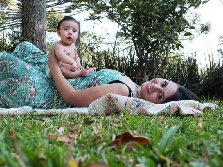 En mor ligger på et teppe med en baby på magen.