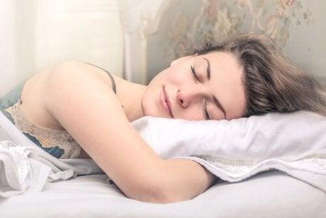 En kvinne sover godt i sengen sin