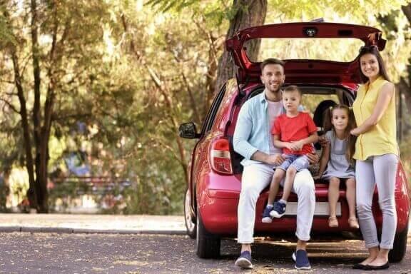 En familie sitter i bagasjerommet til en minibuss.
