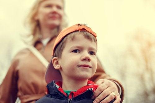 En mor som har en hånd på skulderen til sønnen sin, som et eksempel på overbeskyttende barneoppdragelse.