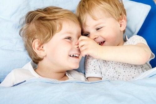 Et par glade brødre i en seng.