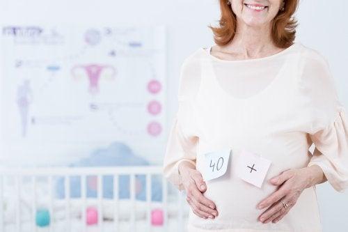 "En eldre gravid kvinne med ""40+"" på magen."