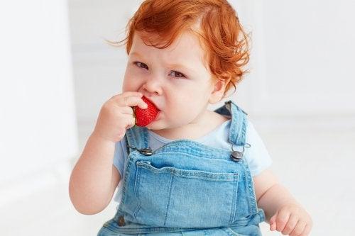 Et barn som spiser jordbær.