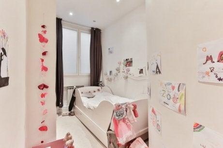 Et barnerom med hvite vegger og mange tegninger
