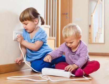Barn som leker med stikkontakter, noe du burde unngå hvis du vil gjøre hjemmet babysikkert.