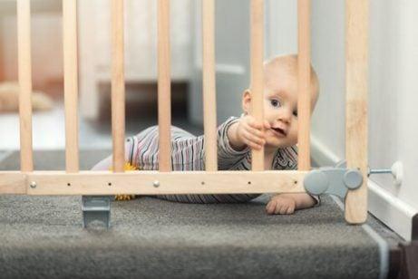 En baby bak en trappegrind, som gjør hjemmet babysikkert.