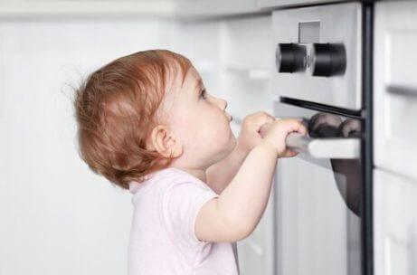 En baby ser på en stekeovn.