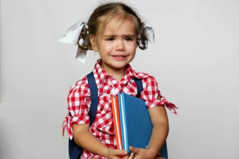 Liten jente med flette i håret og bøker i armene gråter.
