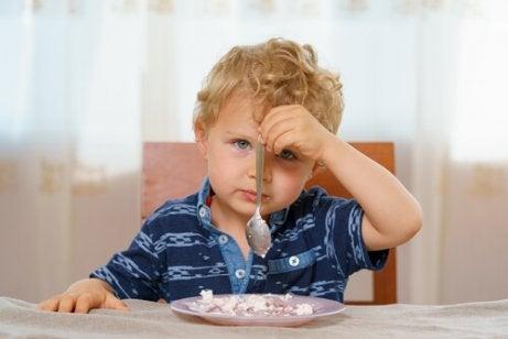 Gutt spiser med venstrehånd