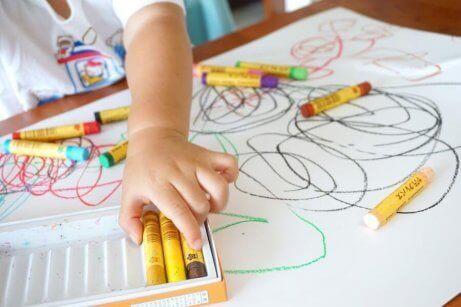 Et barn som bruker mange stifter når hun tegner