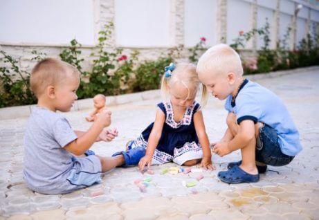 En jente og to gutter leker sammen.