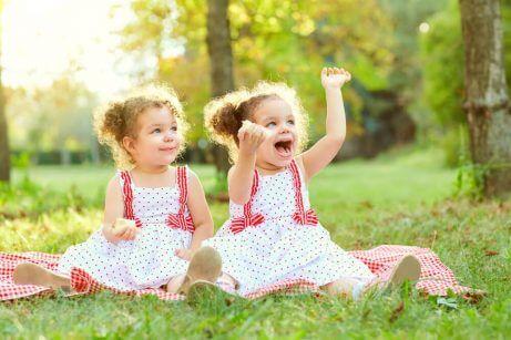 Tvillingjenter leker utendørs.