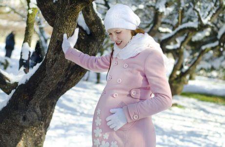 Gravid kvinne i snøen iført vinterklær