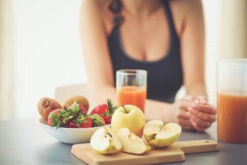 En kvinne som sitter ved et bort som er fullt av sunn mat.