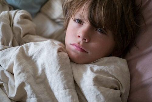 En liten gutt som ligger i senga og er trøtt.