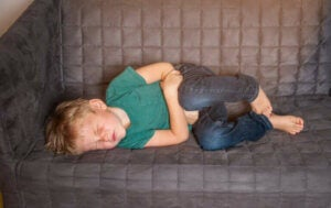 Et lite barn som ligger syk i sofaen