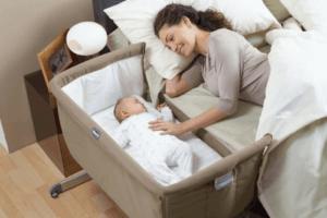 Mor som har babyen sin i en krybbe ved siden av sengen.