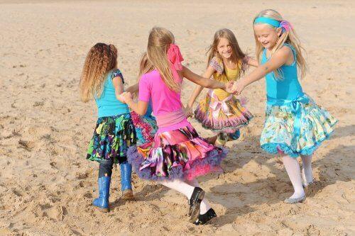 Små jenter i kjoler som løper i ring på stranden.