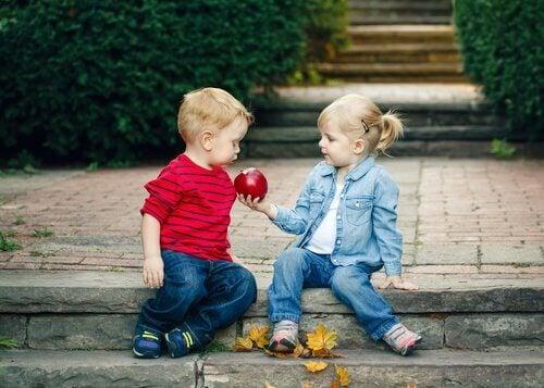To små barn sitter på fortauskanten.